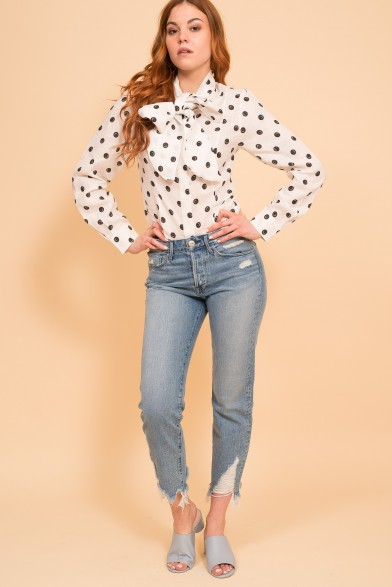 Smiling polka dot blouse with a bow